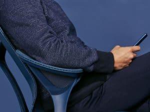 Homme au smartphone assis confortablement sur le fauteuil de bureau Cosm.