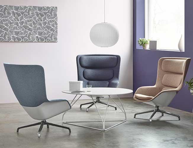 Trois fauteuils de salon Striad autour d'une table ronde dans un espace détente.